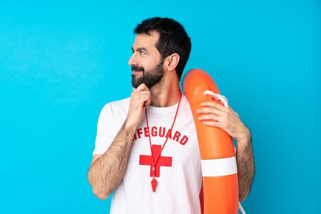 Homem de salva-vidas sobre parede azul isolada, olhando para o lado