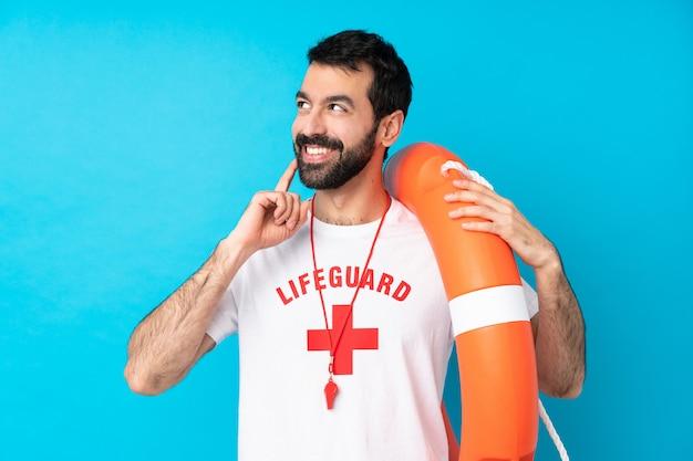 Homem de salva-vidas sobre parede azul isolada, pensando uma idéia enquanto olha para cima