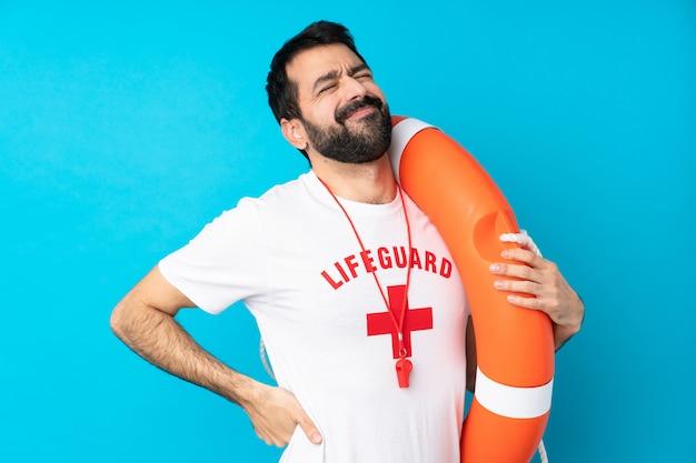 Homem de salva-vidas sobre parede azul isolada, sofrendo de dor nas costas por ter feito um esforço