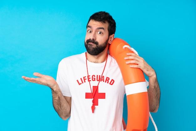 Homem de salva-vidas sobre parede azul isolada, tendo dúvidas ao levantar as mãos