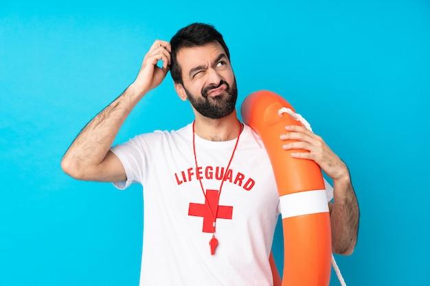 Homem de salva-vidas sobre parede azul isolada, tendo dúvidas enquanto coçar a cabeça