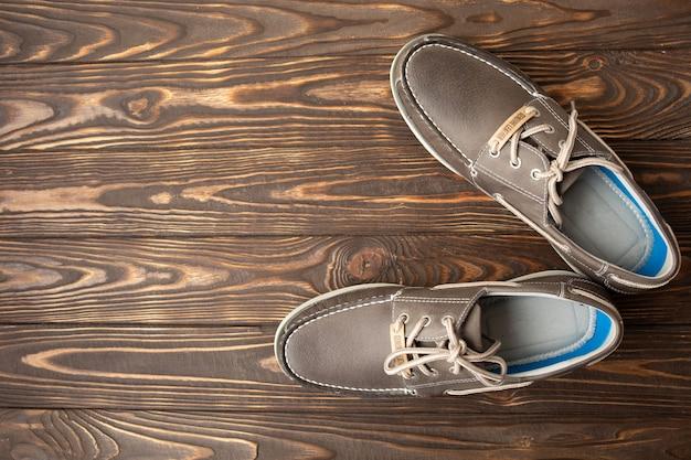 Homem de sapatos marrons, de pé sobre o fundo de madeira