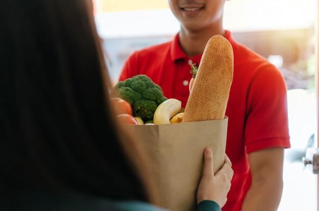 Homem de serviço de entrega de comida inteligente em uniforme vermelho, sorrindo e enviando alimentos frescos