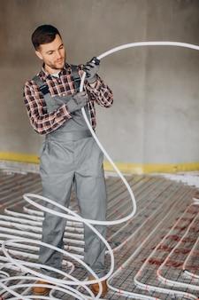 Homem de serviço instalando o sistema de aquecimento da casa sob o piso