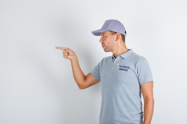 Homem de serviço técnico em camiseta cinza com boné apontando o dedo para o lado