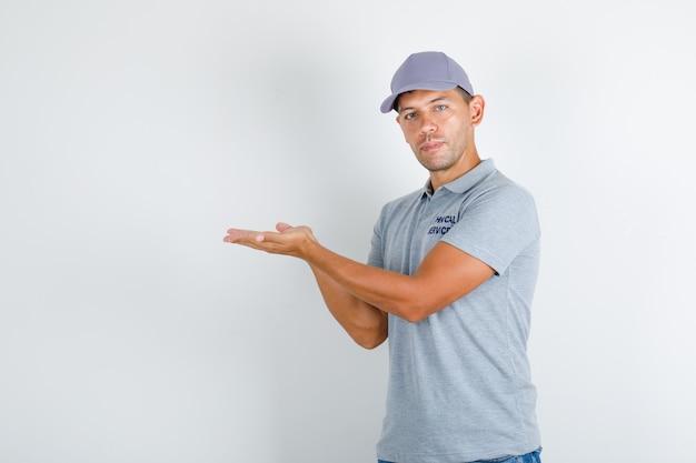 Homem de serviço técnico em camiseta cinza com boné mantendo as palmas das mãos abertas