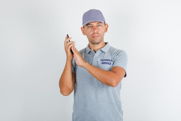 Homem de serviço técnico em camiseta cinza com tampa cobrindo o microfone no smartphone
