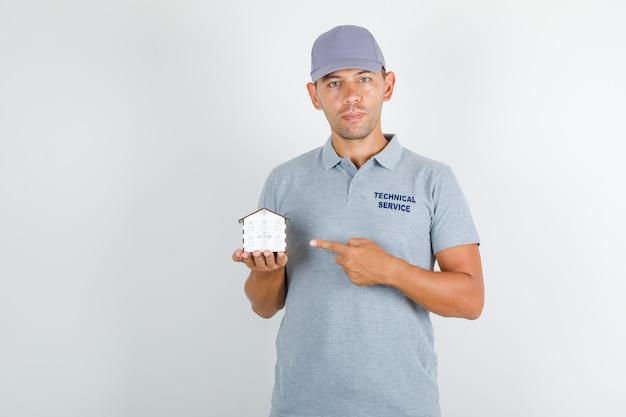Homem de serviço técnico em camiseta cinza com tampa mostrando o modelo da casa com o dedo
