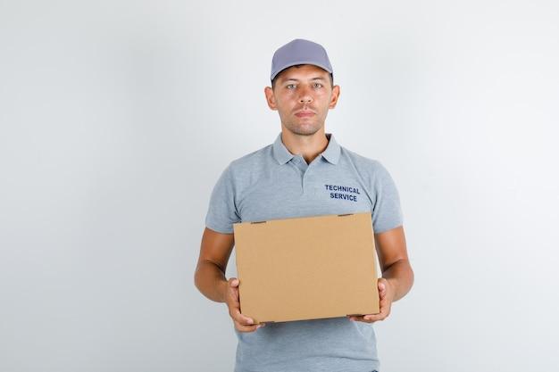 Homem de serviço técnico em camiseta cinza com tampa segurando uma caixa de papelão