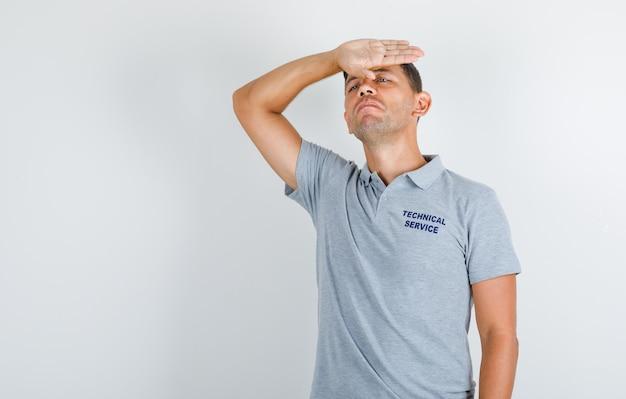 Homem de serviço técnico em pé com a mão na testa em uma camiseta cinza e parecendo desapontado