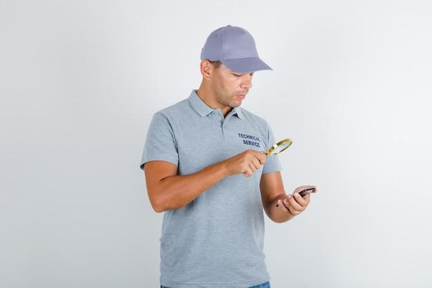 Homem de serviço técnico procurando smartphone sobre lupa em camiseta cinza com tampa