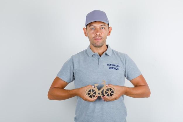 Homem de serviço técnico segurando a bicicleta de brinquedo de madeira em camiseta cinza com tampa, vista frontal.