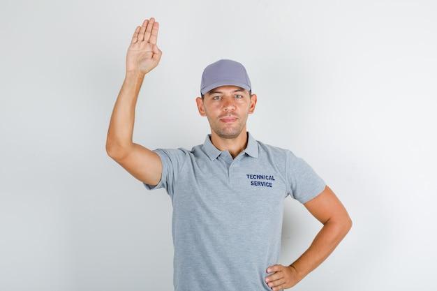 Homem de serviço técnico segurando a palma para cima para saudação em camiseta cinza com tampa e olhando positivo