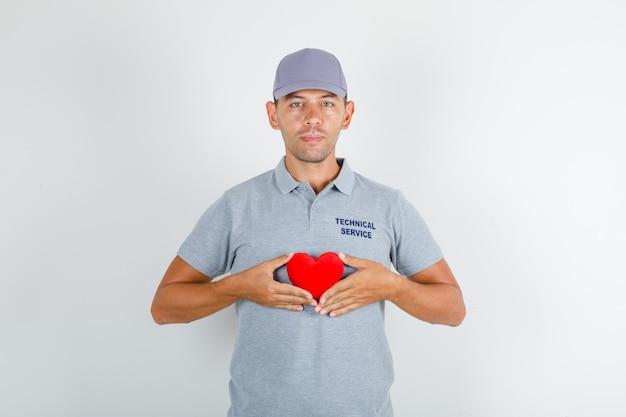 Homem de serviço técnico segurando um coração vermelho em uma camiseta cinza com tampa