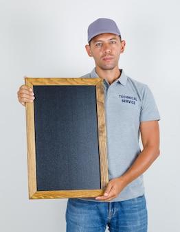 Homem de serviço técnico segurando uma lousa em uma camiseta cinza com tampa