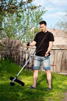 Homem de short com um cortador de escova profissional, cortar a grama no quintal. gramado verde, cerca velha como pano de fundo. tempo ensolarado de primavera.