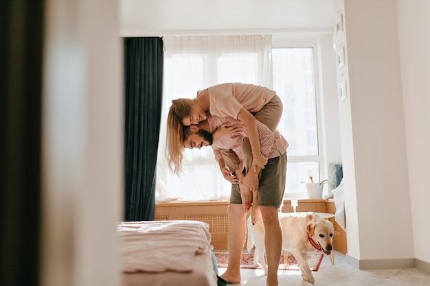 Homem de shorts cáqui está segurando sua jovem esposa nas costas enquanto o cachorro caminha ao lado. os amantes desfrutam de um fim de semana despreocupado em seu apartamento.