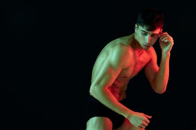 Homem de shorts posando de preto com um torso bíceps inflado