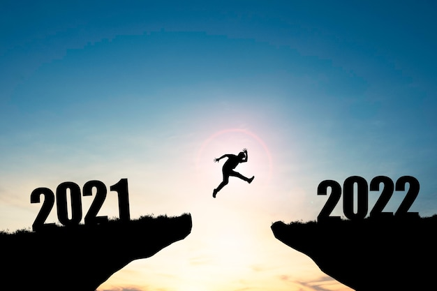 Homem de silhueta pulando de penhasco de 2021 para penhasco de 2022 com céu azul e luz do sol, preparação de novo destino de negócios de desafio e vida para o ano novo.