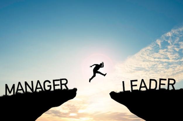 Homem de silhueta pulando de penhasco de gerente em penhasco de líder na nuvem e no céu azul. mude o comportamento e a mentalidade para o conceito de liderança