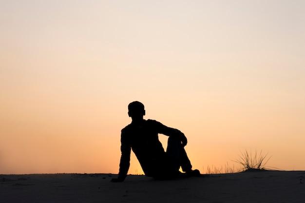Homem de silhueta sentado no fundo do céu