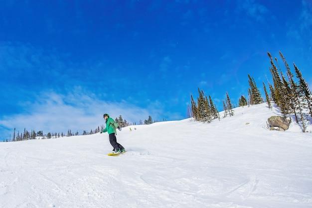 Homem de snowboard nas montanhas sheregesh.