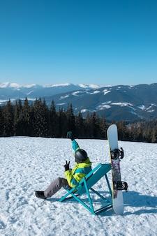 Homem de snowboard sentado em uma cadeira, apreciando a vista da montanha, copie o espaço