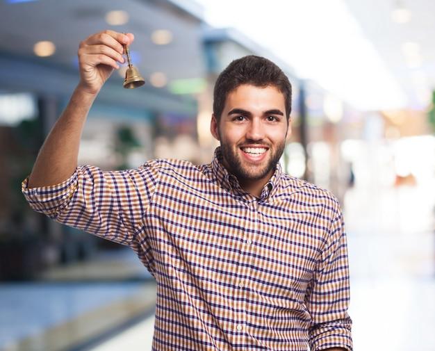 Homem de sorriso com um pequeno sino