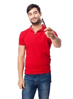 Homem de sorriso com uma chave na mão