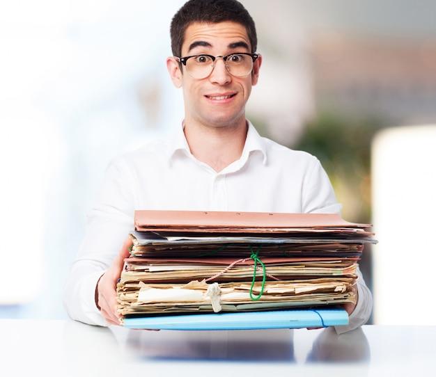 Homem de sorriso com uma pilha de papéis nas mãos