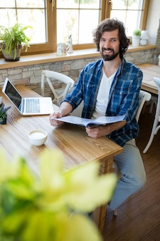 Homem de sorriso do menu segurando na cafetaria