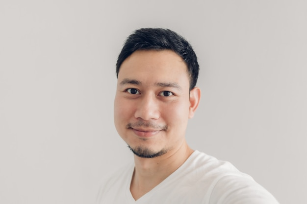 Homem de sorriso está tomando selfie de si mesmo com t-shirt branca