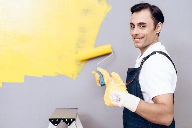 Homem de sorriso no labber na parede cinzenta da pintura uniforme.