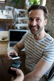 Homem de sorriso pagando com a tecnologia nfc no telefone móvel