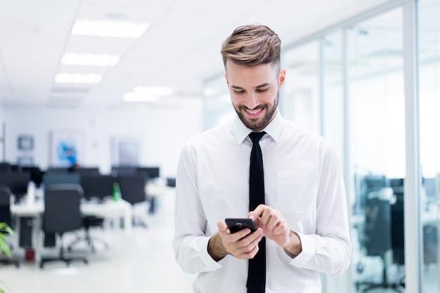 Homem de sorriso que datilografa em seu telefone