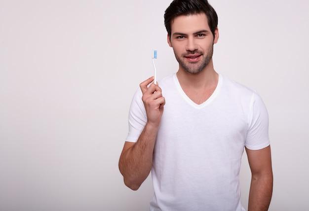 Homem de sorriso que escova seus dentes com uma escova de dentes no branco.