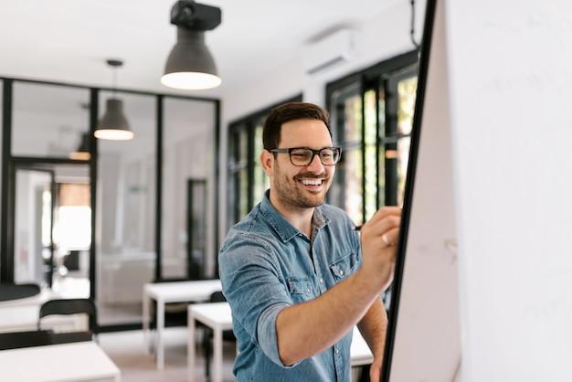 Homem de sorriso que escreve no whiteboard.