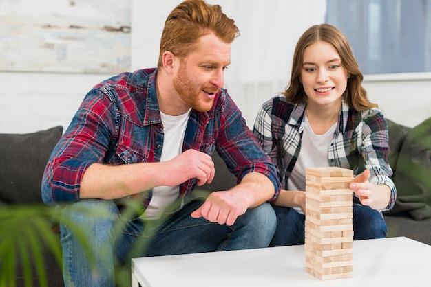 Homem de sorriso que olha a mulher que joga o jogo da pilha dos blocos de madeira em casa
