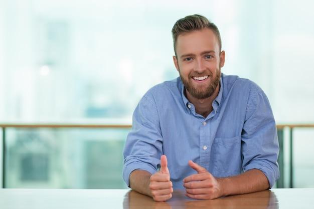 Homem de sorriso senta-se na tabela do café e gesticulando