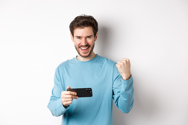 Homem de sorte ganhando no videogame para celular, segurando o smartphone e dizendo que sim, triunfando com a bomba de punho, em pé sobre um fundo branco.