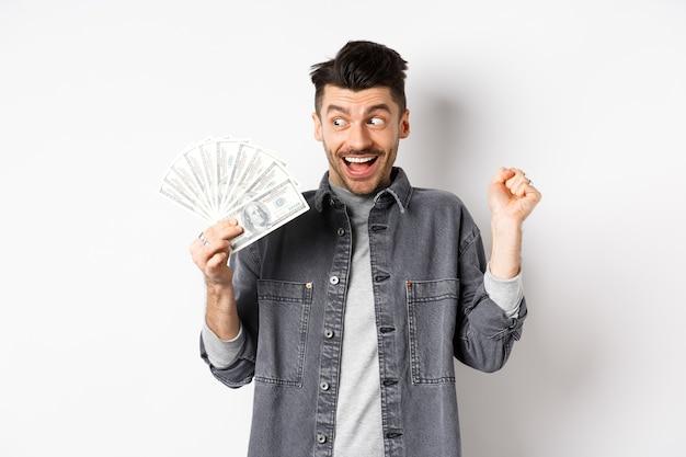 Homem de sorte ganhando prêmio em dinheiro e grito de emoção, olhando para as notas de dólar felizes, de pé no fundo branco.