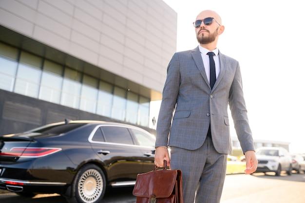 Homem de sucesso de terno com uma pasta no fundo de um carro caro