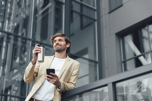 Homem de sucesso em um elegante terno segurando em uma mão um smartphone moderno e uma xícara de café na outra
