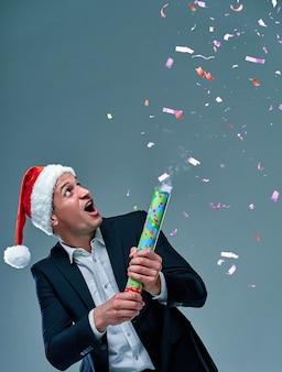 Homem de sucesso em um terno sobre um fundo cinza em um boné de papai noel comemora o ano novo. tiroteio em estúdio.