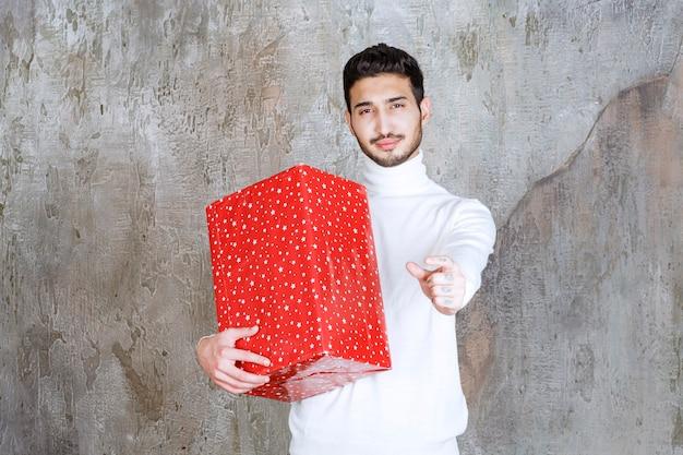 Homem de suéter branco segurando uma caixa de presente vermelha com pontos brancos e mostrando um sinal positivo com a mão.