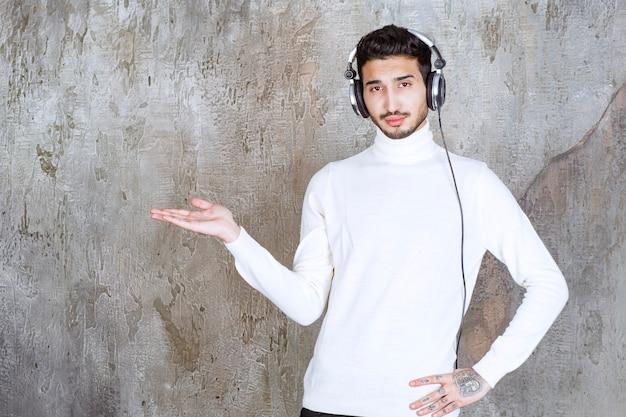 Homem de suéter branco usando fones de ouvido, ouvindo música e mostrando algo ao redor.
