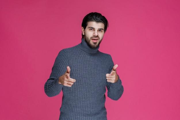 Homem de suéter cinza, apontando algo ou apresentando alguém usando o dedo indicador.