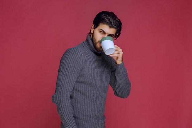 Homem de suéter cinza, bebendo café da caneca.