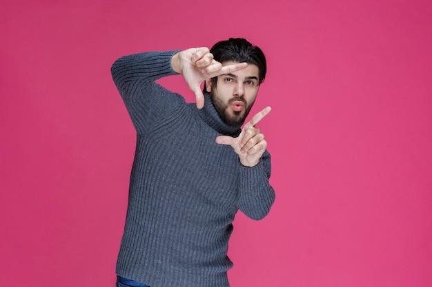 Homem de suéter cinza fazendo sinal de mão de moldura de foto.