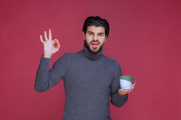 Homem de suéter cinza segurando uma caneca de café e apreciando o sabor.